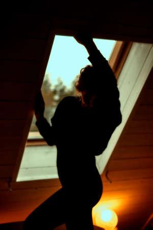 Playful seductive young woman silhouette near window in dark bedroom