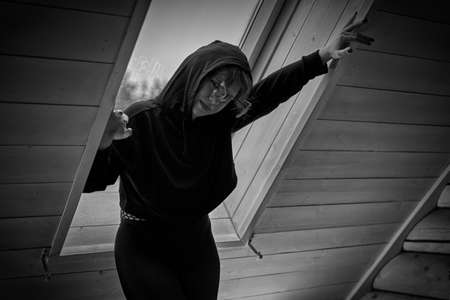 Young woman in black jacket with hood near window in dark bedroom