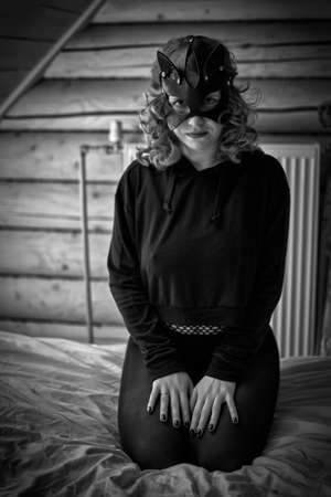 Seductive cat-woman in sexy costume in artistic grayscale bedroom settings