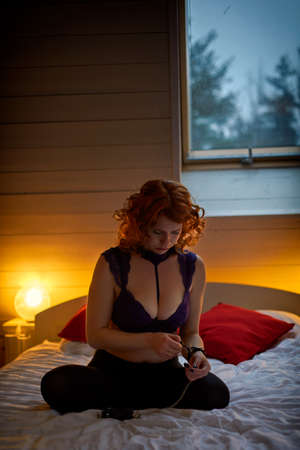 Young playful redheaded woman in handcuffs in cozy country house interior Stockfoto