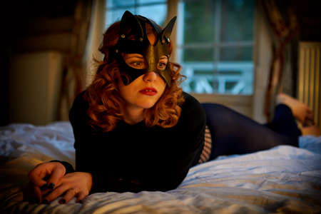 Seductive playful cat-woman in sexy costume lying on bed Imagens