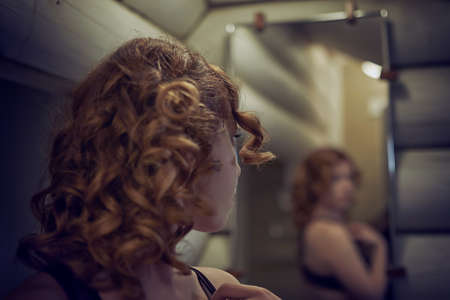Curly hair redheaded young woman looking at herself in the mirror in the bathroom Imagens