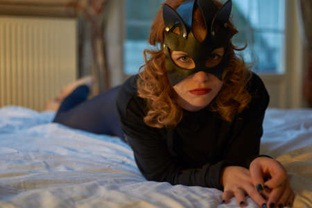 Artistic portrait of young redheaded woman in seductive cats mask Imagens