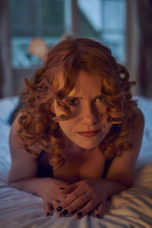 Young playful redheaded woman in sexy dress and leather harness on a bed in country house