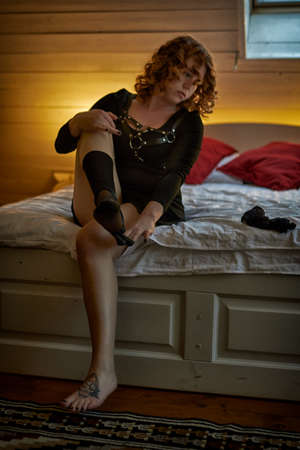 Artistic portrait of young woman putting up stockings in morning bedroom Banque d'images