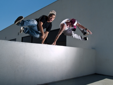 two free-runners jumping over a wall