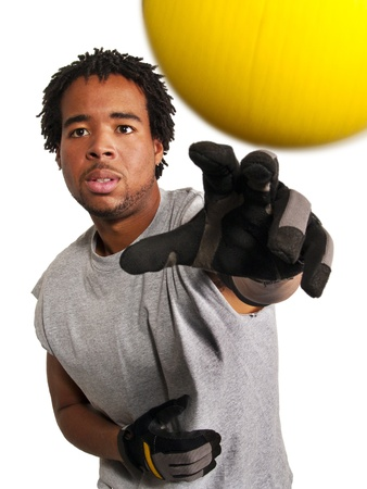 dodge ball player throwing a yellow ball at viewer Stock Photo