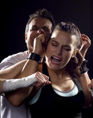 defensa personal: Mujer joven del ajuste que lucha un hombre
