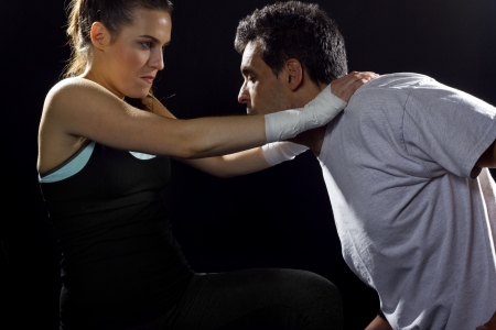 self defense: young fit woman fighting a man