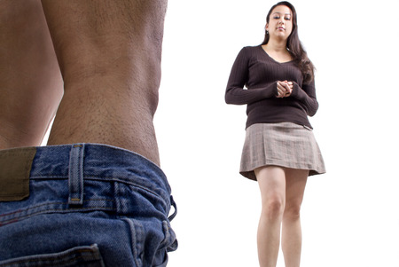 embarassed man with pants down while woman makes fun of his manhood Stock Photo