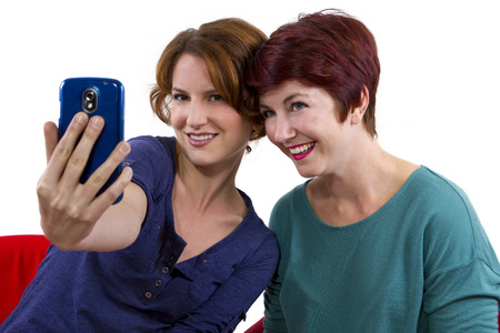 two women taking self portraits with a cell phone photo