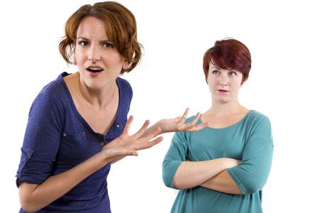 desconfianza: dos mujeres de raza blanca sosteniendo y desconfiando entre s� Foto de archivo