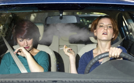young female smoking while driving inside the car Stock Photo