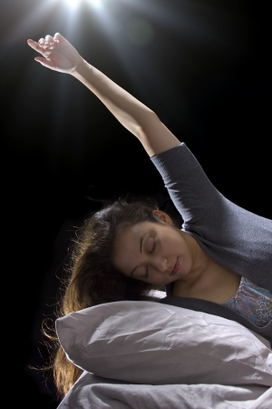 abduct: creepy glowing orb hovering over a woman sleeping in bed Stock Photo