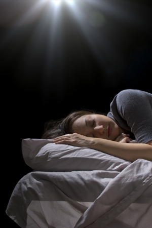 abducted: creepy glowing orb hovering over a woman sleeping in bed Stock Photo