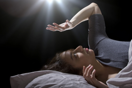 creepy glowing orb hovering over a woman sleeping in bed photo