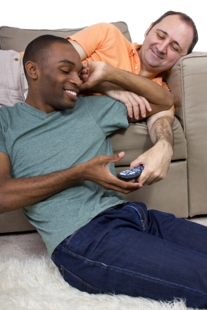 two gay lovers relaxing at home in the livingroom photo