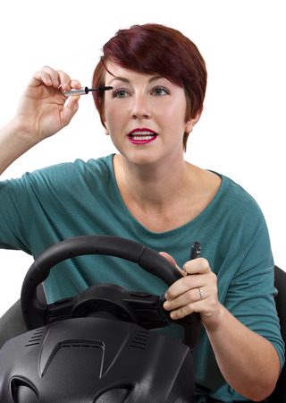 young red head woman applying make up while driving Stock Photo - 23491605