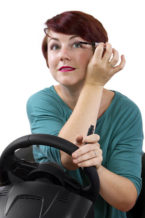 red head woman: young red head woman applying make up while driving Stock Photo