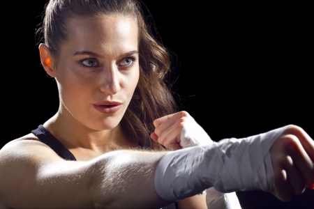 martial arts woman: female MMA fighter punching   black background