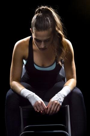 female MMA fighter in a black background