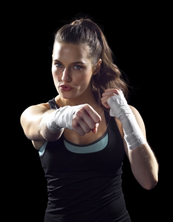 martial arts: female MMA fighter punching   black background