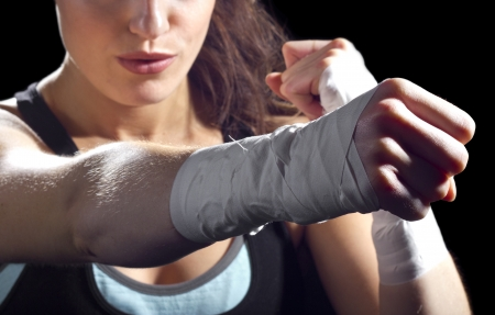 mixed martial arts: female MMA fighter punching   black background