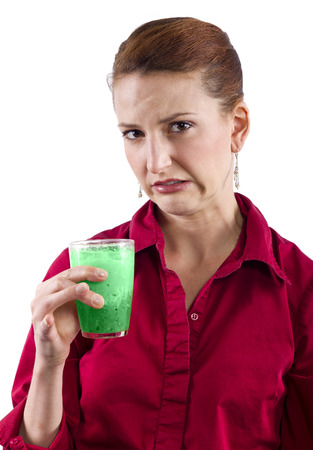 unpleasant: woman grossed out by green vegetable juice