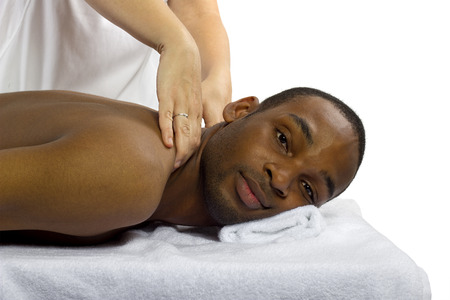 young female masseuse treating young male client with massage photo