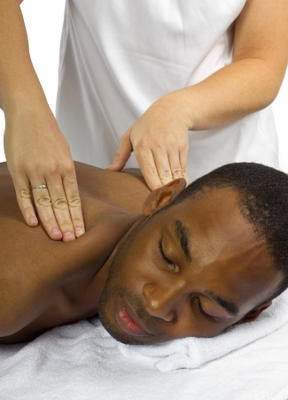 young female masseuse treating young male client with massage Stock Photo - 23513068