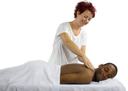 young female masseuse treating young male client with massage Stock Photo - 23513109