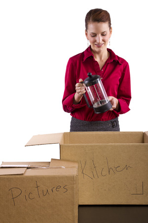 stuff: woman packing stuff in moving boxes