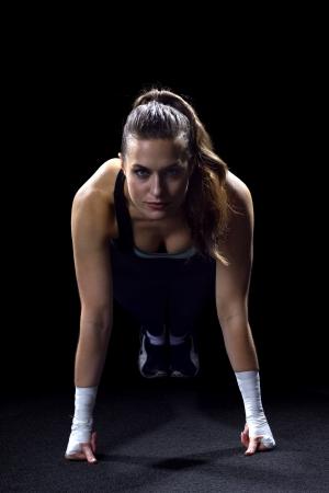 fit vrouw doet push ups op zwarte achtergrond