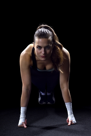 fit woman doing pushups on black background photo