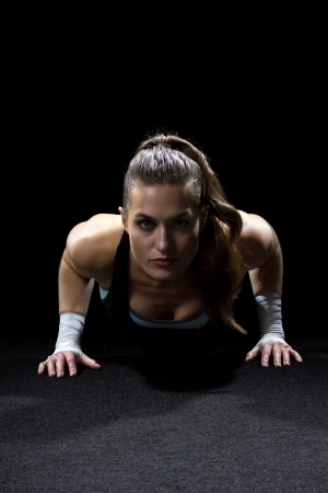 woman working out: fit woman doing pushups on black background Stock Photo