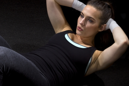 weight training: fit woman doing situps on a black background
