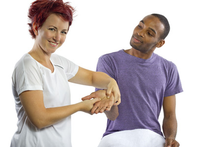 young female masseuse applying pressure on male clients hand