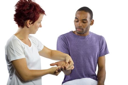 young female masseuse applying pressure on male clients hand photo