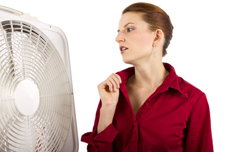 indoors: Businesswoman cooling off with a fan