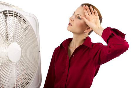 refreshing: Businesswoman cooling off with a fan
