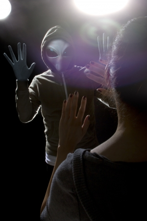 x files: Gray alien with lights behind abducting a young woman Stock Photo
