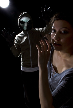 abduct: Gray alien with lights behind abducting a young woman Stock Photo