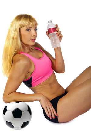 futbol: giovane calciatore femminile bionda acqua potabile da una bottiglia