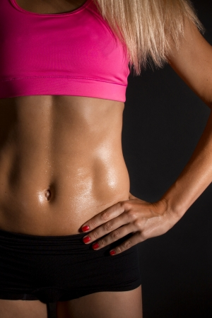 muscle woman: close up of sweaty female abdominal muscles