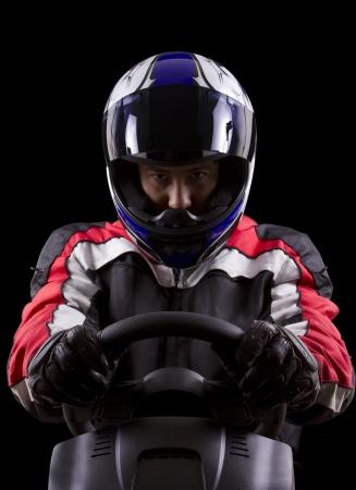 racerwearing red racing suit and blue helmet on a steering wheel