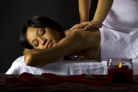 young female getting a massage in a dark intimate room Stock Photo - 23840279