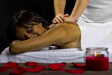 young female getting a massage in a dark intimate room Stock Photo - 23840281