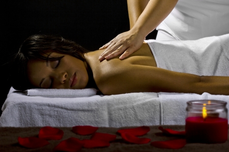 young female getting a massage in a dark intimate room Stock Photo - 23840285