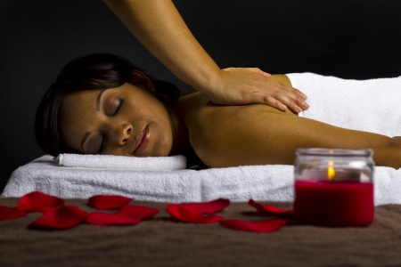 young female getting a massage in a dark intimate room Stock Photo