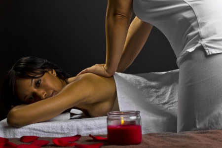 young female getting a massage in a dark intimate room photo